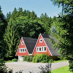 Bild einer roten Wanderhütte mit doppeltem Spitzdach im Wald.